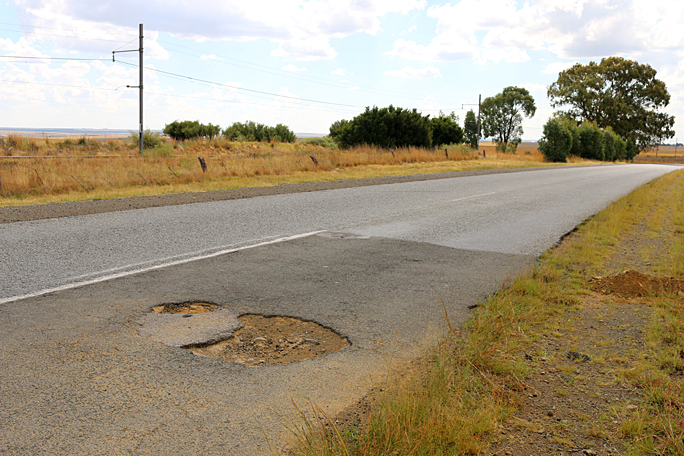 This is the pothole which killed the tire on my rental car. It appears that this section of the road was repaired at least once before. Photograph ©2015 by Brian Cohen.