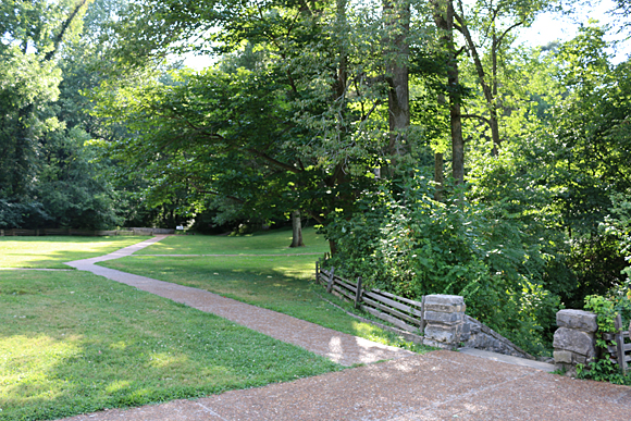 The path to the left leads to where the Boundary Oak tree once stood in the woods; while the stairs with the stone entrance on the right leads down to Sinking Spring. Photographs ©2014 by Brian Cohen.