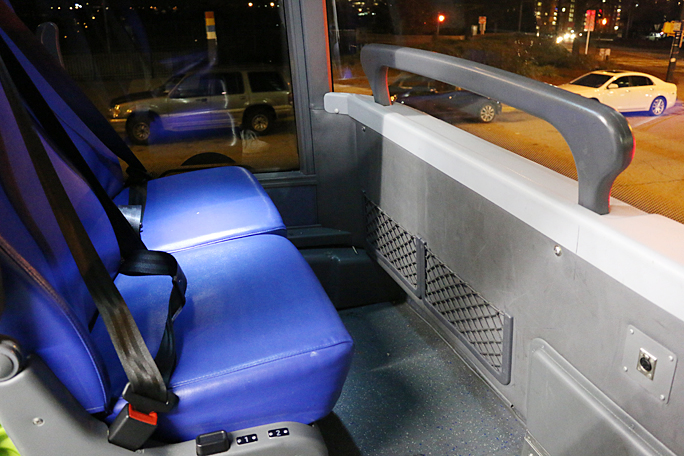 "These are the two seats across the aisle from mine on the upper deck of a Megabus. Although a ""cut-out"" is provided for feet, there is not much legroom. The black button on the side allows the seat to be reclined. Note the ample amount of viewing room thanks to the abundance of windows. Photograph ©2015 by Brian Cohen."